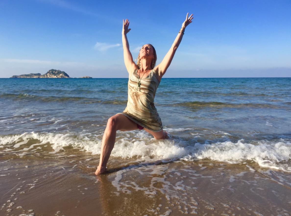 Frau beim Yoga in der leichten Meeresbrandung am Sandstrand
